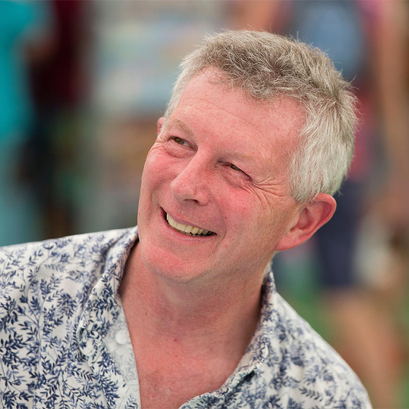 a photo of Stephen Moss, a white man with grey hair in his 60s. Stephen is smiling and wearing a white shirt with small blue leaf print.